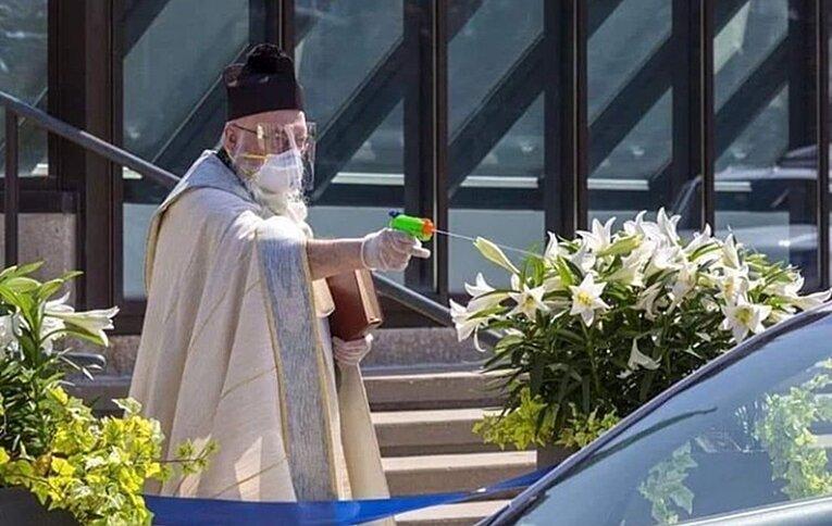 Bir rahip, sosyal mesafeye uyarak kutsama yapıyor.